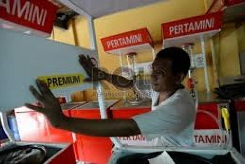 Penjual melakukan pengisian bahan bakar minyak (BBM) jenis premium di salah satu kios pengisian