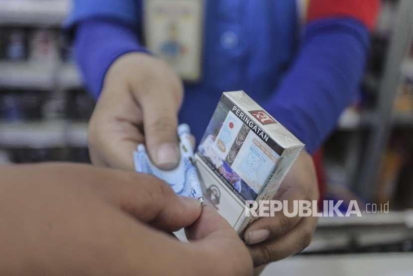 Penjual melayani pembeli rokok di Jakarta, Rabu (19/9).