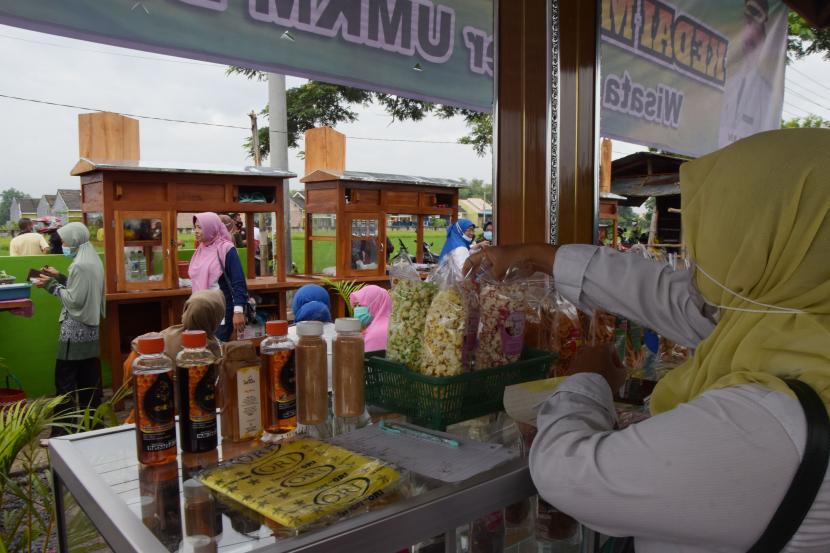 Penjual melayani pembeli saat pembukaan pusat penjualan hasil produk Usaha Mikro Kecil Menengah (UMKM), di Kelurahan Banjarejo, Kota Madiun, Jawa Timur, Sabtu (13/2/2021).