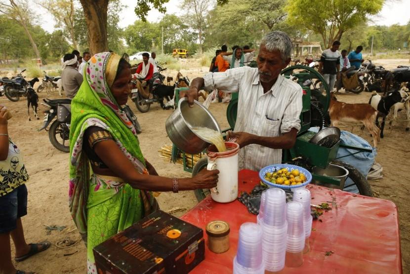 Penjual minuman tebu di hari yang panas di pinggiran Rae Bareli, Uttar Pradesh, India, Rabu (12/6). Suhu udara di utara dan barat India mencapai 48 derajat Celsius.