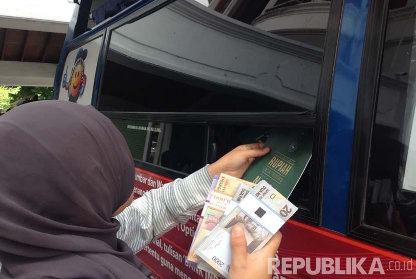 Penukaran uang di mobil keliling BI di halaman parkir Republika, Jakarta, Jumat (24/6). (Republika/Maman Sudiaman)