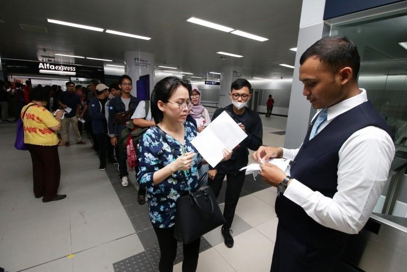 Penumpang antre untuk uji coba publik Moda Raya Terpadu (MRT) Jakarta, Jumat (22/3/2019).