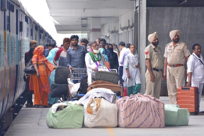 Penumpang berdiri dengan barang-barang mereka setelah turun dari Samjhauta Express, kereta yang menghubungkan Delhi di India dan Lahore di Pakistan, di Attari, sebuah kota di sepanjang perbatasan dengan Pakistan, Punjab, India utara, Kamis (8/8).