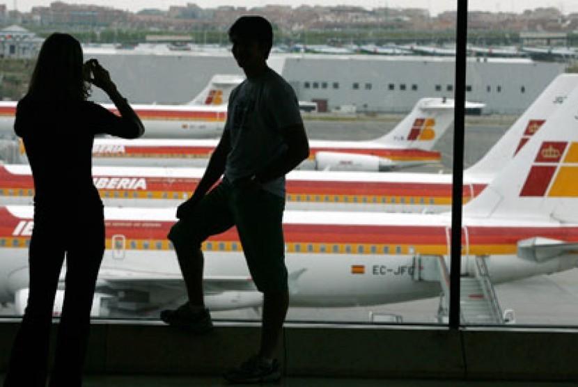 Penumpang berpose di sebuh bandara di Madrid, Spanyol.