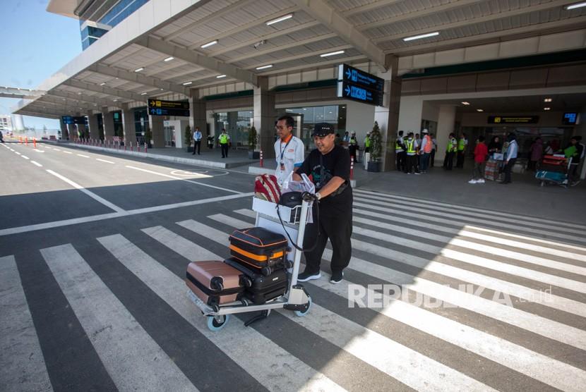 Penumpang keluar dari area bandara seusai mendarat dengan pesawat komersial.