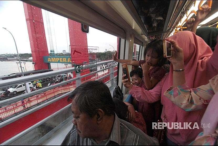 Penumpang melihat Jembatan Ampera dari dalam gerbong kereta Api Ringan atau Light Rapid Transit (LRT) ketika menuju Jakabaring, Palembang, Sumatera Selatan, Selasa (28/8).