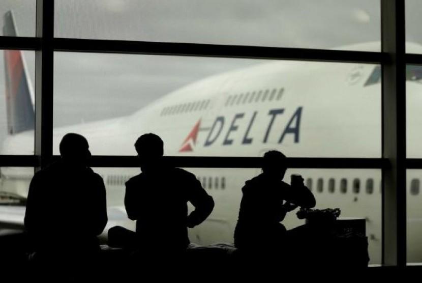 Penumpang menunggu pesawat di Bandara LaGuardia, New York. Badai Sandy membuat maskapai harus membatalkan total seluruh jadwal penerbangan sejak Ahad. Kini, maskapai AS, salah satunya Delta Air Lines, berupaya kembali membuka layanan.
