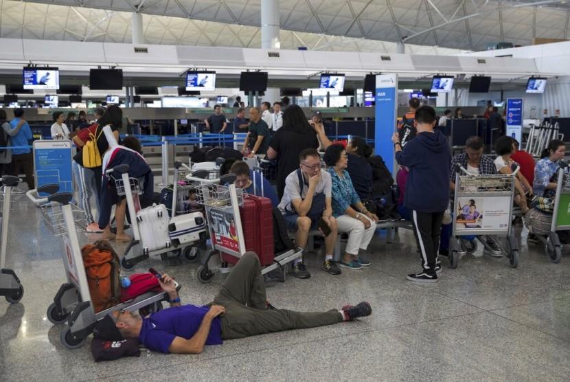 Penumpang telantar di terminal keberangkatan di Bandara Internasional Hong Kong di Hong Kong, Selasa (13/8).
