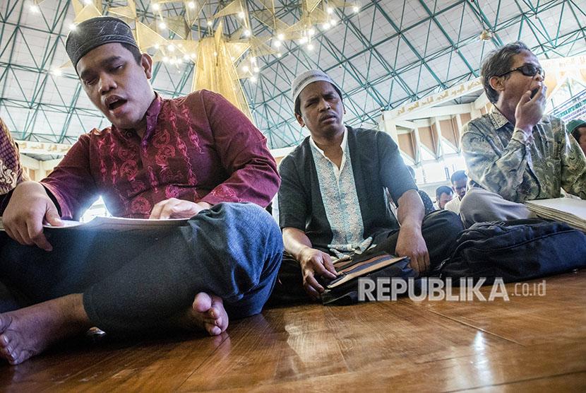 Penyandang tunanetra membaca Alquran saat mengikuti Tadarus Nasional Quran Braille di Masjid Al Ukhuwah, Bandung, Jawa Barat, Sabtu (2/6).