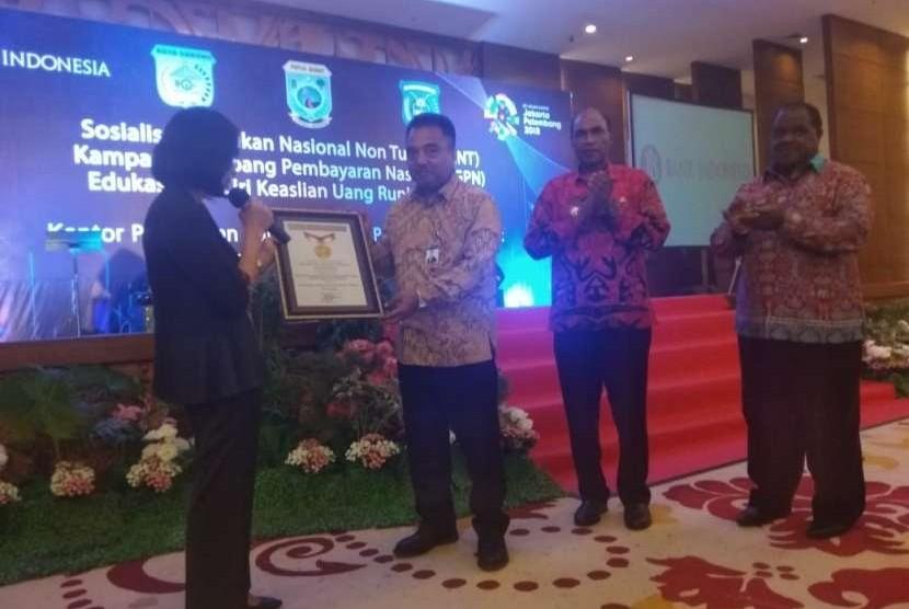 Kepala BI Provinsi Papua Barat Donny Heatubun menerima piagam rekor MURI tentang pembagian uang eletronik kepada pelajar terbanyak dan pembelian kebutuhan sekolah dengan menggunakan uang elektronik terbanyak di Sorong, Papua Barat, Jumat (10/8).