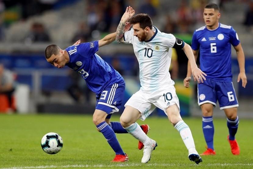 Penyerang Argentina Lionel Messi (tengah) berebut bola dengan pemain Paraguay Miguel Almiron pada laga Grup B Copa America 2019.