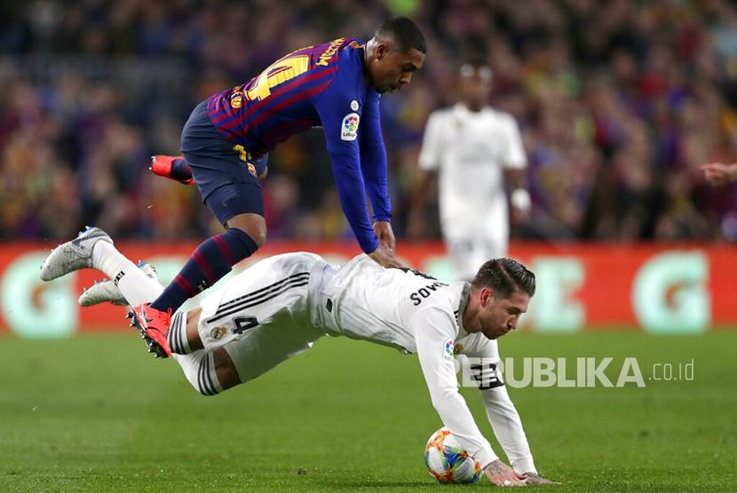 Penyerang Barcelona Malcom berduel dengan bek Real Madrid Sergio Ramos pada leg pertama semifinal Copa del Rey di stadion Camp Nou di Barcelona, Spanyol, Rabu (6/2/2019).