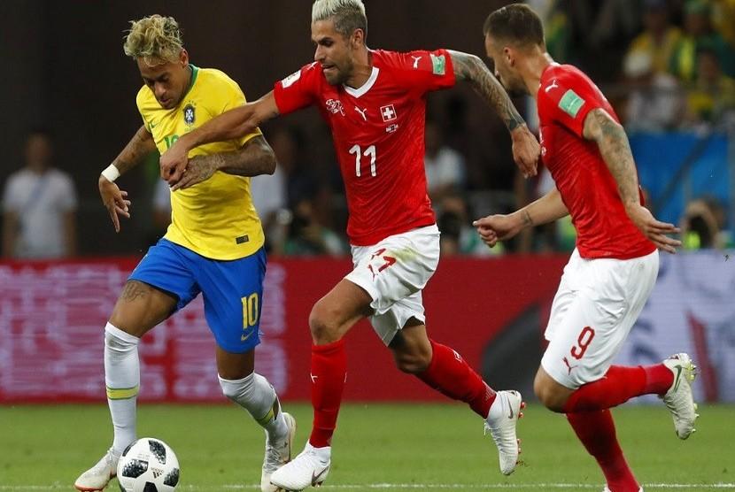 Penyerang Brasil Neymar (kiri) berebut bola dengan pemain Swiss, Valon Behrami dalam pertandingan di Grup E antara Brasil melawan Swiss, di Rostov Arena, Rusia, Ahad (17/6)