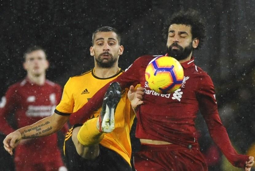 Penyerang Liverpool Mohamed Salah berusaha melindungi bola dari rebutan pemain Wolverhampton Wanderers.