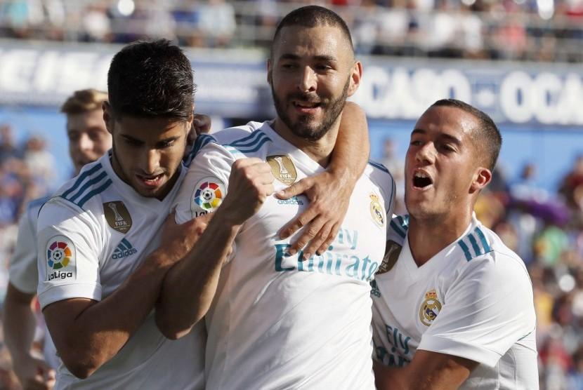 Penyerang Real Madrid asal Prancis Karim Benzema (tengah) merayakan golnya ke gawang Getafe bersama rekan setimnya, Marco Asensio (kiri) dan Lucas Vazquez pada lanjutan La Liga Spanyol di Stadion Coliseum Alfonso Perez, Sabtu (14/10) waktu setempat.