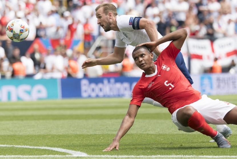 Penyerang timnas Inggris Harry Kane (baju putih) dihalangi bek Swiss Manuel Akanji pada laga perebutan peringkat ketiga UEFA Nations League, Ahad (9/6).