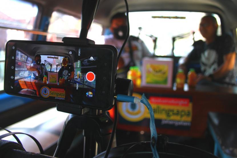 Penyiar mewancarai seorang narasumber di sebuah angkutan kota yang diubah menjadi studio siniar (podcast) keliling di Malang, Jawa Timur, Rabu (22/9/2021). Studio podcast keliling dari angkutan tersebut dioperasikan untuk mempromosikan keunikan kawasan wisata setempat dalam upaya pemulihan ekonomi wisata.