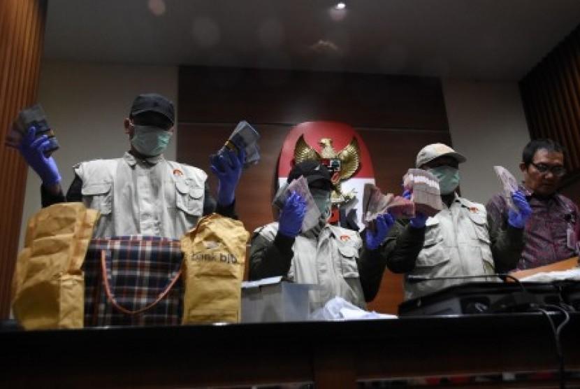 Penyidik Komisi Pemberantasan Korupsi (KPK) didampingi Wakil Ketua KPK Saut Situmorang (kanan) menunjukkan barang bukti sitaan saat konferensi pers terkait Operasi Tangkap Tangan (OTT) terhadap anggota DPR Komisi XI Fraksi Demokrat Amin Santono bersama beberapa orang lainnya di Bandara Halim Perdanakusuma, Jakarta Timur, di Gedung KPK, Jakarta, Sabtu (5/5).