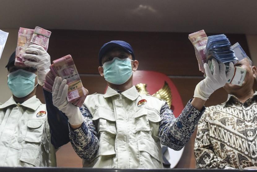 Penyidik KPK menunjukkan barang bukti uang hasil OTT Hakim Tipikor Bengkulu saat konferensi pers di gedung KPK, Jakarta, Kamis (7/9).