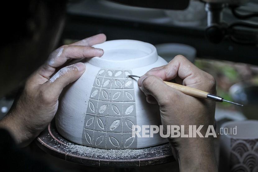 Perajin melakukan sgraffito atau proses aplikasi corak pada kerajinan keramik di Pekunden Pottery, Bojongsari, Depok, Jawa Barat, Selasa (21/9/2021). Produksi keramik rumahanberbahan tanah liat bakaran tinggi tersebut dijual dengan harga Rp50 ribu hingga Rp3 juta per buah tergantung ukuran dan tingkat kesulitan.