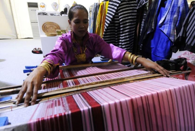 Perajin memeragakan pembuatan kain tenun tradisional khas Pulau Buton dalam pameran Indonesia Creative Power 2013 di Epicentrum Kuningan, Jakarta, Rabu (27/11). Kementerian Pariwisata dan Eonomi Kreatif (Kemenparekraf) mengungkapkan sektor ekonomi kreatif