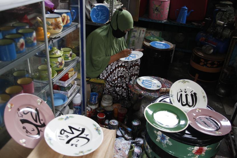 Perajin menyelesaikan lukisan kaligrafi Arab pada piring keramik di Fairus Art, Pasar Kliwon, Jawa Tengah.