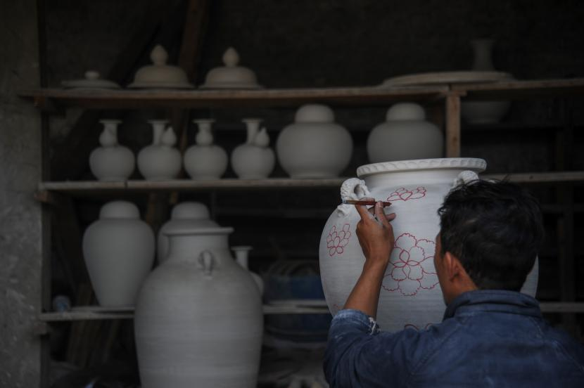 Perajin menyelesaikan produksi guci keramik di Kampung Cibuntu, Desa Mekarbakti, Kabupaten Sumedang, Jawa Barat, Rabu (22/9/2021). Produk keramik yang dijual dari harga puluhan ribu hingga puluhan juta rupiah tersebut diminati oleh pasar dalam negeri hingga dapat menjual ke berbagai negara di Amerika dan Afrika.