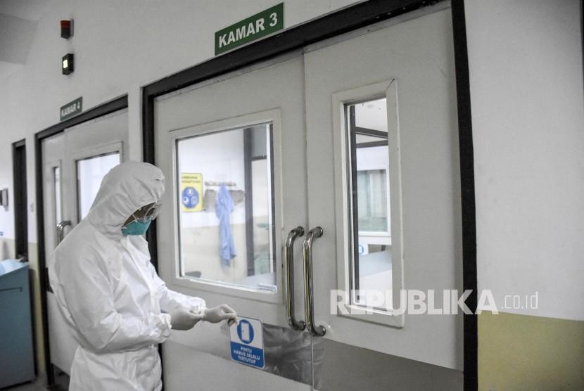 Perawat mengenakan pakaian alat pelindung diri (APD) berada di Ruang Isolasi Infeksi Khusus (RIIK) untuk pasien yang terkena visrus corona di Rumah Sakit Hasan Sadikin (RSHS), Kota Bandung, Jumat (24/1).