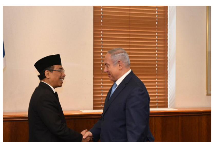Israel Prime Minister Benjamin Netanyahu shakes hands with Yahya Cholil Staquf.