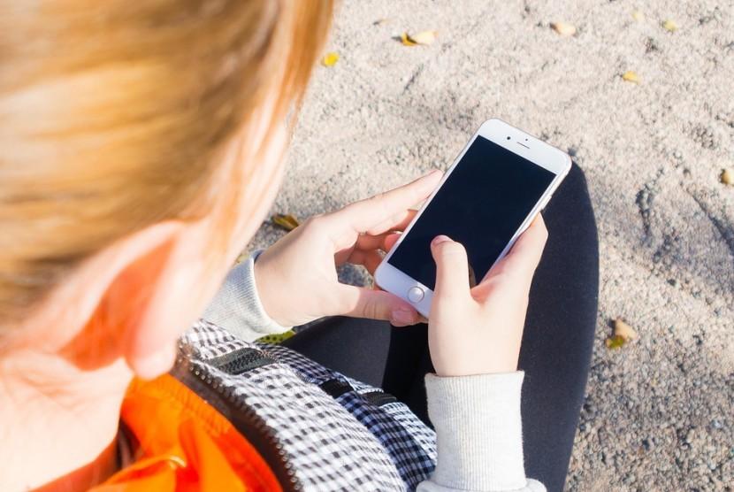 Perempuan memegang ponselnya.