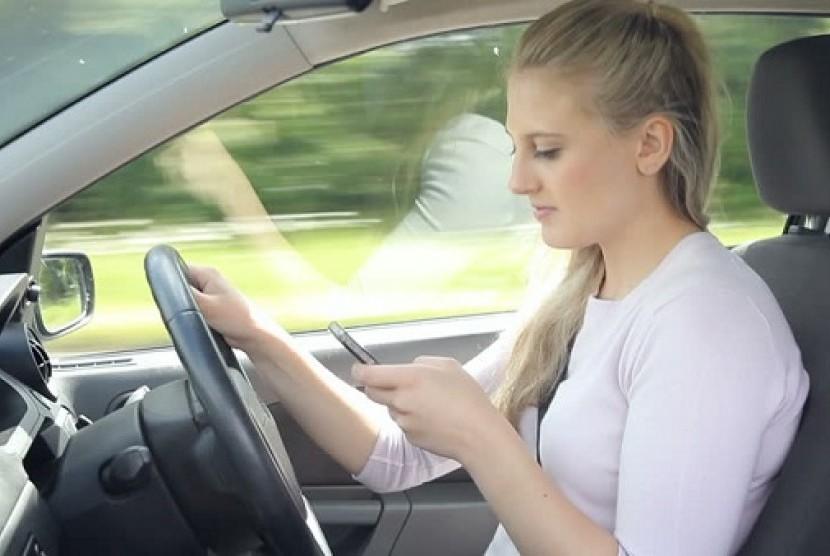 Perempuan menyetir sambil main ponsel. Ilustrasi