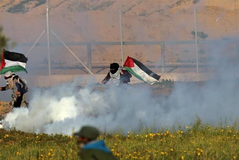 Perempuan Palestina berlari membawa bendera Palestina untuk menghindari serangan gas air mata yang dilancarkan tentara Israel.