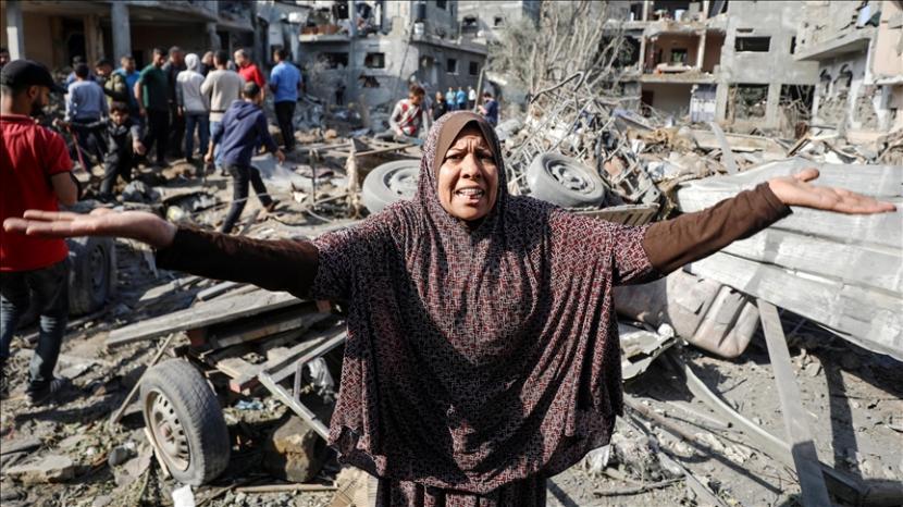 Perempuan Palestina mencari sisa-sisa barang miliknya tengah reruntuhan bangunan yang hancur akibat serangan Israel di Beit Hanoun, Gaza pada 14 Mei 2021.