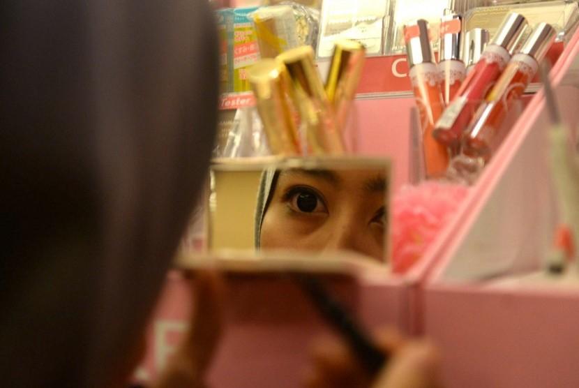 Perempuan sedang mencoba produk kosmetik.