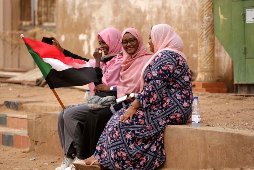Perempuan Sudan memegang bendera nasional ketika mereka merayakan di jalan-jalan setelah penandatangan deklarasi konstitusional antara dewan militer yang berkuasa dan pengunjuk rasa, di Khartoum, Sudan, 4 Agustus 2019.