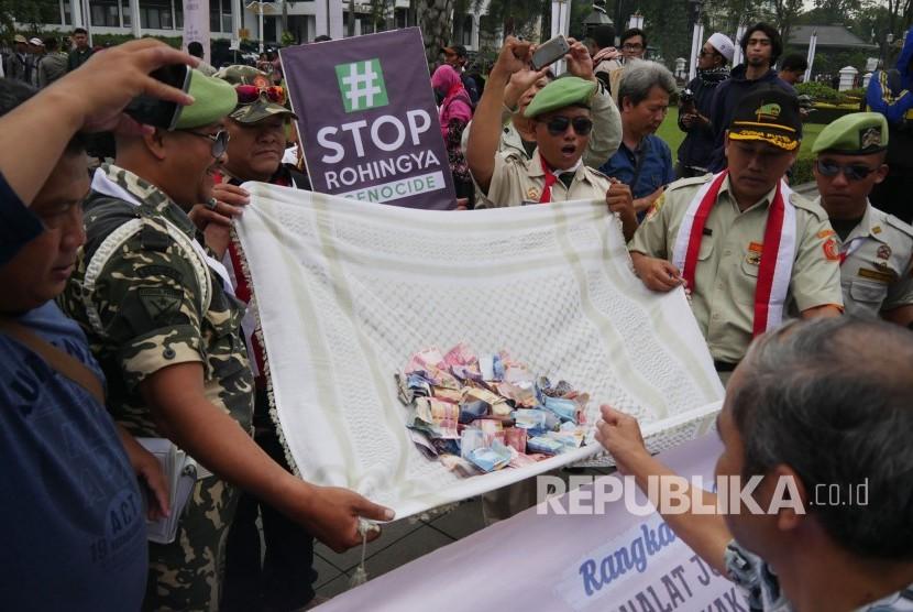 Perserta aksi memberikan donasi pada aksi masyarakat peduli Rohingya, di depan Gedung Sate, Kota Bandung, Jumat (8/9).