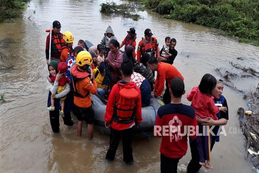Personel Basarnas Kendari mengevakuasi korban banjir bandang di wilayah terisolir yang terjebak di atap rumahnya di Desa Tanggawuna, Konawe, Sulawesi Tenggara.