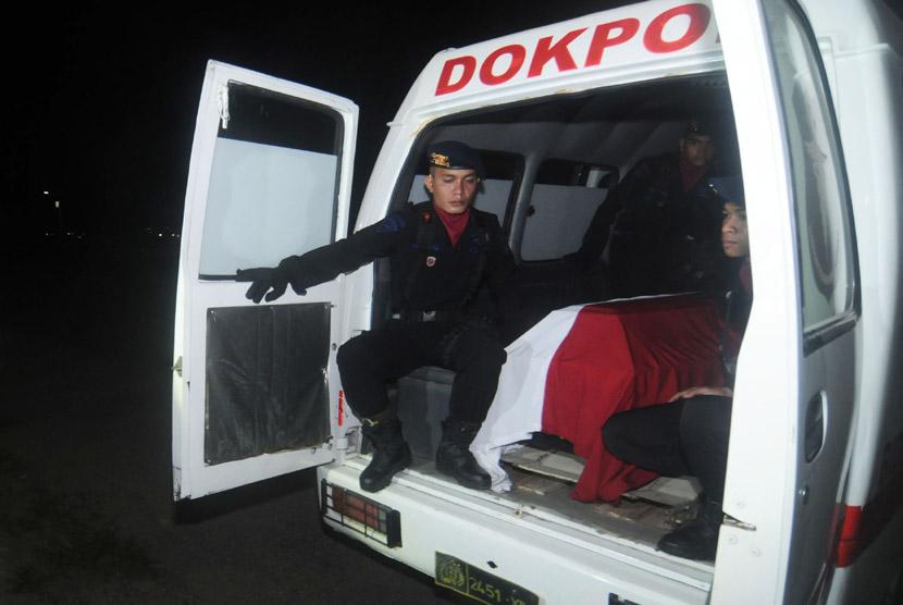 Personel Brimob berada di samping peti jenazah Bharada I Putu Satria saat akan diterbangkan ke kampung halamannya di Bandara Mutiara Palu, Sulawesi Tengah, Jumat (7/2).