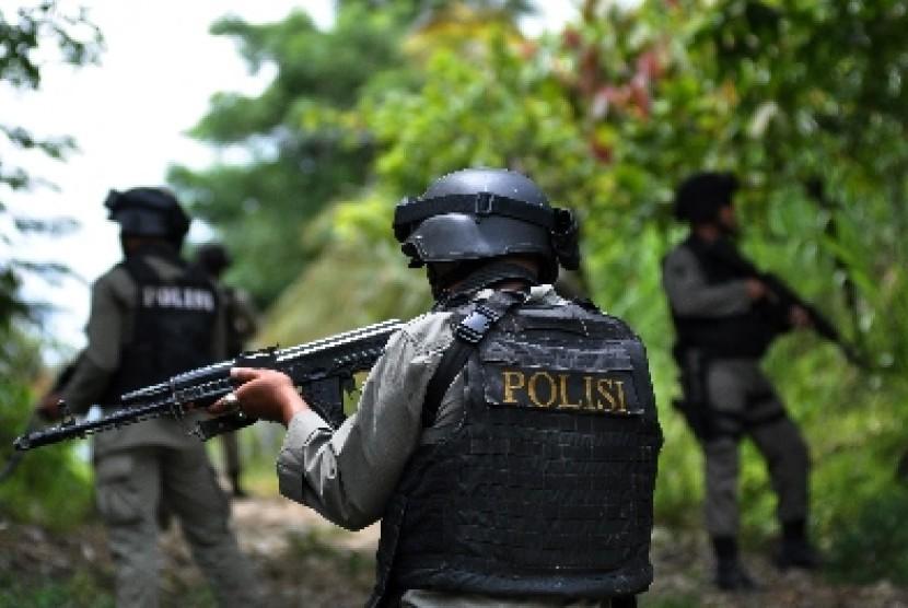 Personel Brimob berpatroli memburu teroris di Desa Tangkura, Poso Selatan, Sulawesi Tengah, Sabtu (14/3).