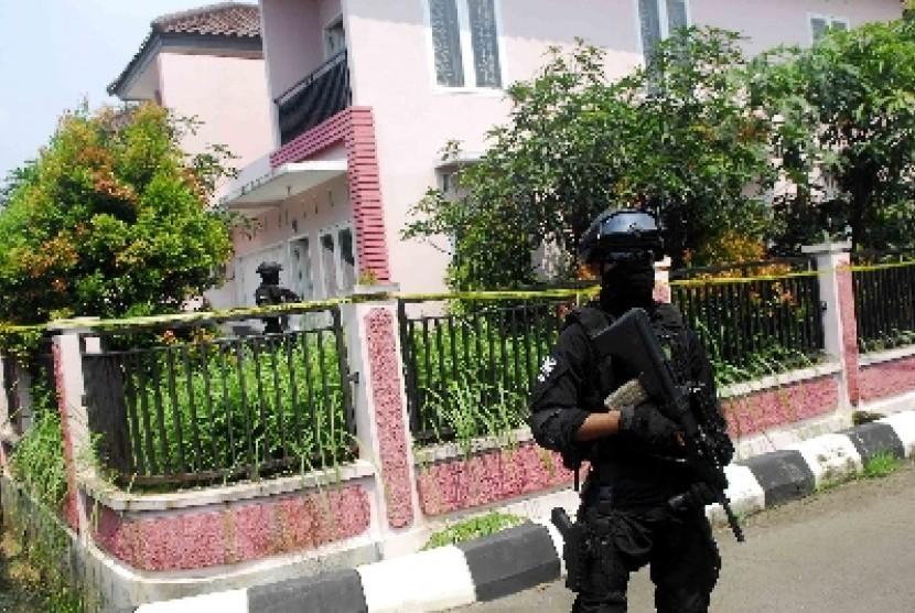 Personel Densus 88 berjaga di depan rumah terduga teroris di Jakarta Selatan, Ahad (22/3).