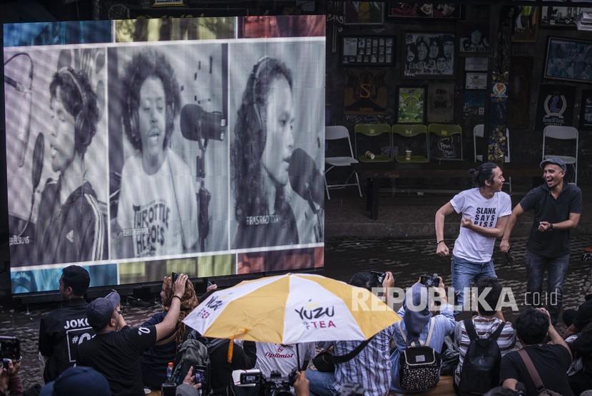 Personel grup band Slank, Bimbim (kedua kanan) dan Ivanka (kanan) berjoget saat pemutaran video klip bertajuk #BARENGJOKOWI di markas Slank, Gang Potlot, Jakarta, Jumat (15/3/2019).