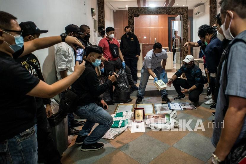 Personel kepolisian berbaju sipil menggelar barang bukti saat dilakukan penggeledahan di bekas markas Front Pembela Islam (FPI), Petamburan, Jakarta, Selasa (27/4/2021). Tim Densus 88 Antiteror menggeledah tempat tersebut pascapenangkapan mantan Sekretaris Umum Front Pembela Islam (FPI) Munarman terkait kasus dugaan tidak pidana terorisme.
