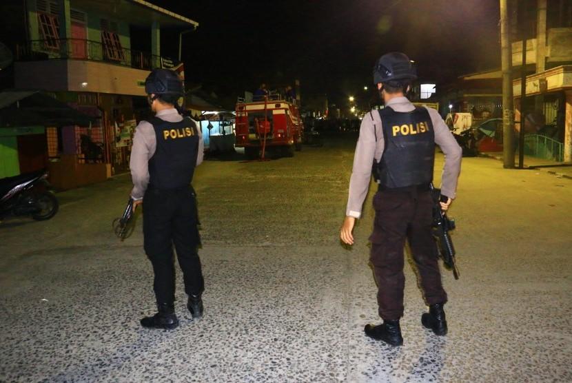 Personel kepolisian berjaga di lokasi terjadinya ledakan yang diduga bom saat penggerebekan terduga teroris di kawasan Jalan KH Ahmad Dahlan, Pancuran Bambu, Sibolga Sambas, Kota Siboga, Sumatera Utara, Selasa (12/3).