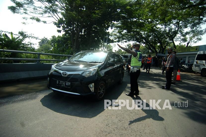 Personel kepolisian mengarahkan warga untuk berputar arah saat pengetatan mudik mulai diberlakukan (ilustrasi)