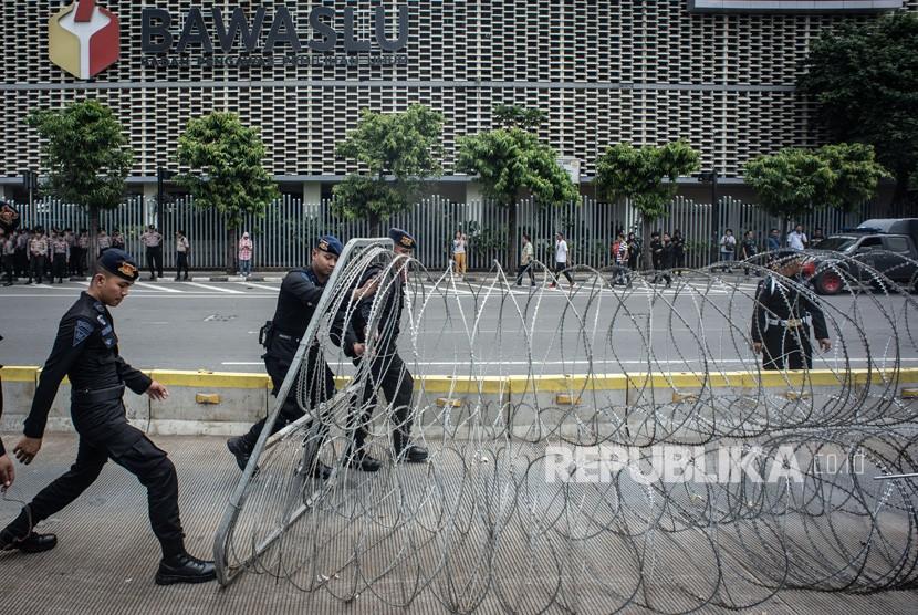 Personel korps Brimob memasang kawat berduri di kawasan Kantor Bawaslu, Jakarta, Selasa (21/5/2019).