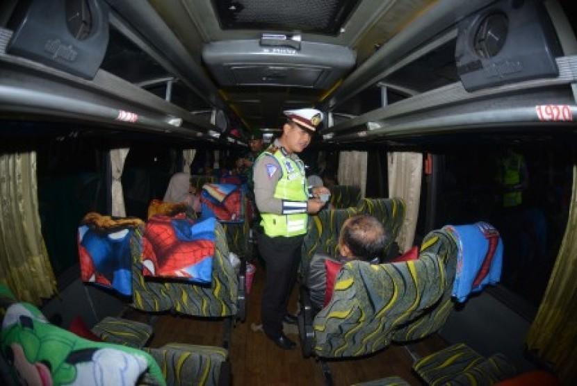 Personel Polri melakukan pemeriksaan identitas penumpang bus di jalan raya Pantura Situbondo, Jawa Timur, Sabtu (18/5/2019) malam. Pemeriksaan kendaraan beserta penumpang dan barangnya tersebut untuk mengantisipasi pergerakan massa yang akan berangkat ke Jakarta menjelang pengumuman hasil rekapitulasi suara Pemilu 2019 di kantor KPU.