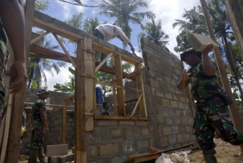 Personel TNI dari satuan Zeni Korem 081/DSJ Madiun melakukan rehabilitasi rumah korban terdampak bencana banjir bandang di Pacitan, Jawa Timur, Ahad (10/12). Sebanyak 420 unit dari total 6.603 rumah terdampak bencana banjir bandang dan tanah longsor daerah itu mulai dibangun bertahap dengan target tuntas Januari 2018.