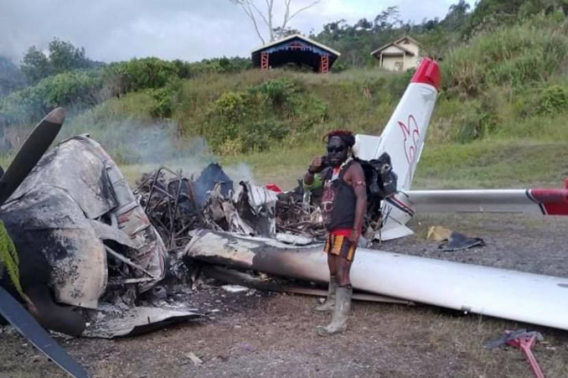 Personel TPNPB-OPM berpose di bangkai pesawat milik Mission Aviation Fellowship (MAF) dibakar di kampung Pagamba, Distrik Mbiandoga, Intan Jaya, Papua, Rabu (6/1).