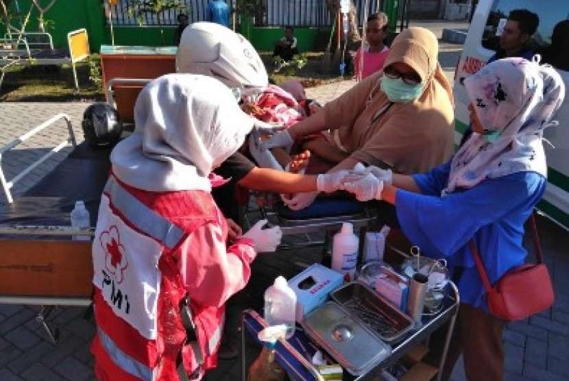 Personil Palang Merah Indonesia sedang mengobati korban selamat gempa bumi lombok