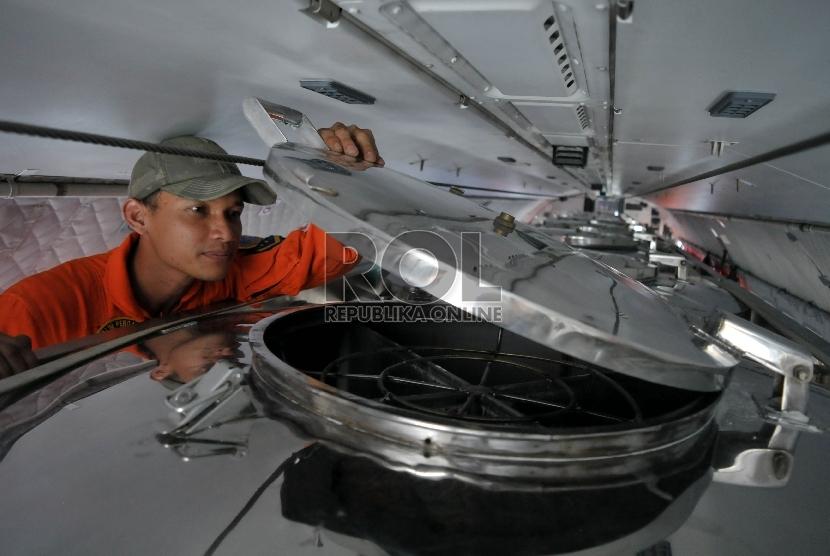 Personel TNI AU mengecek sejumlah tabung sebelum melakukan teknologi modifikasi cuaca (TMC) di pesawat CN-292 milik TNI AU sebelum diberangkatkan di Lanud Halim Perdanakusuma, Jakarta.